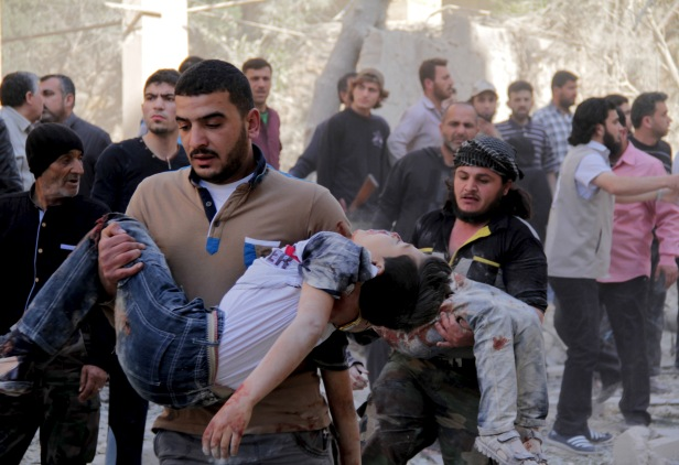 Men carry injured schoolchildren after what activists said was a barrel bomb dropped by forces loyal to Syria's President Bashar al-Assad and hit a school and a residential building in Seif al-Dawla neighborhood of Aleppo